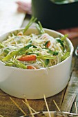 Rice noodles and vegetables cooked in a wok