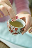 Putting a rose petal in a cup of tea