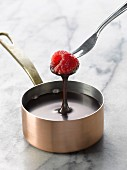 Dipping a raspberry into a saucepan of melted chocolate