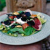A salad with dried salted ham, truffles, mozzarella and broad beans
