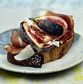 Dry-cured ham with figs and Parmesan cheese on a slice of grilled bread