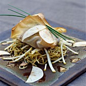 Stuffed filo pastry on fried noodles and finely sliced apple