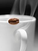 Dampfende Kaffeetasse und Kaffeebohne
