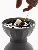 Adding a lump of sugar to a bowl of black coffee