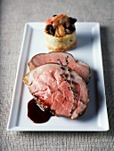 Leg of lamb cooked in a casserole dish with potato and mushroom timbale