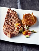 Marinated and grilled pork backbone steak with citrus fruit zests