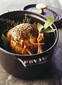 Pigeon cooked in a casserole dish with herbs