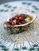 Hot oyster with hazelnut butter and pomegranate seeds and coriander