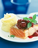 Thick piece of salmon with cherry sauce and mashed potatoes