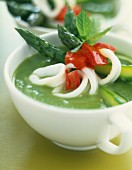 Cream of green asparagus soup with squid and red peppers