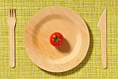 Wooden plate,knife and fork with a cherry tomato