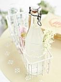 Eine Flasche Holunderblütenlimonade in weißem Körbchen