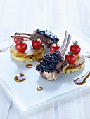 Lamb chops coated with tapenade, polenta cakes and cherry tomatoes