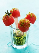 Tomato sorbet lollipops coated with crushed pistachios