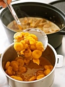 Cooked carrots and apricots in a cooking pot