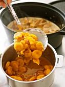 Gegarte Möhren und Aprikosen in Kochtopf schöpfen