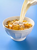 Pouring milk onto a bowl of cornflakes