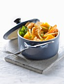 Casserole dish of gambas with mango and ginger