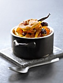 Casserole dish of baked apple with dried fruit and vanilla