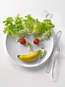 Plate of vegetables and mini banana in the shape of a face