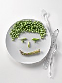 Plate of peas and asparagus in the shape of a face