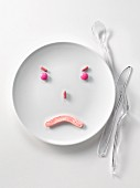 Plate of pink candies in the shape of a sad face