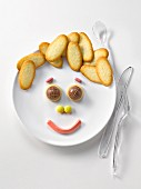 Plate of Langues de chat biscuits and candies in the shape of a happy face