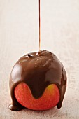 Coating an apple with melted chocolate