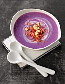 Cream of Vitelotte potato soup with crushed hazelnuts and flaked grisons meat