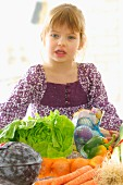 Young girl infront of a table of vegetables