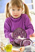 Young girl cutting a red cabbage