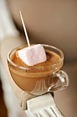 Dripping a marshmallow in a cup of chocolate cream
