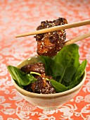 Sweet and sour pork with sesame seeds and spinach shoots