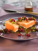 Thick pieces of salmon with pistachios and rose petals