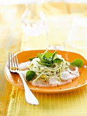 Thinly sliced fish and spaghettis with spinach and lemon