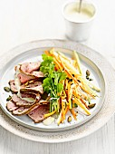 Sliced roast beef with celery, carrots, squash seeds and herbs
