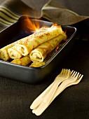 Rolled banana pancakes flambé