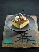 Portion of green tea cake decorated with coconut balls and gold leaf