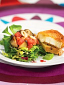 Fried goat's cheese coated in breadcrumbs with mixed salad and raspberry dressing