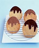 Plätzchen in Eierform mit flüssiger Schokolade