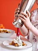 Young girl spraying whipped cream onto stewed mirabelle plums with cinnamon