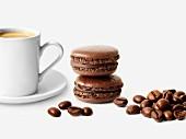 Schokoladen-Macarons, Tasse Kaffee und Kaffeebohnen