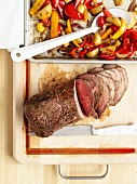 Roast beef with oven-baked potatoes and red and yellow peppers