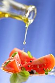 Pouring olive oil onto sliced tomatoes