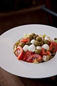Tomato, mozzarella ball, olive and caper salad