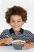 Junge isst ein Schälchen Frühstücksflocken
