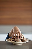 Child's hand stealing a cookie from a plate of cookies