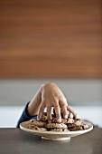 Kinderhand stibitzt Plätzchen vom Teller