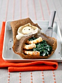 Buckwheat pancake with spinach, seafood and goat's cheese