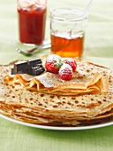Stacked pancakes with summer fruit,chocolate jars of jam and icing sugar